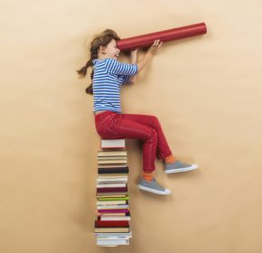 Happy girl is playing with group of books in studio