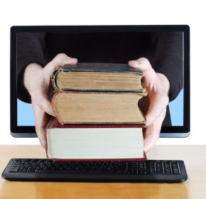 Arms reaching through computer screen holding a stack of three vintage books. Conceptual composite shot to illustrate online delivery of books, knowledge or education.